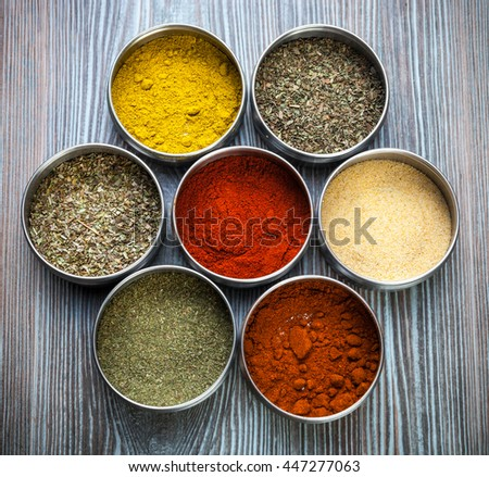 Various spices and herbs in metal containers on wooden table