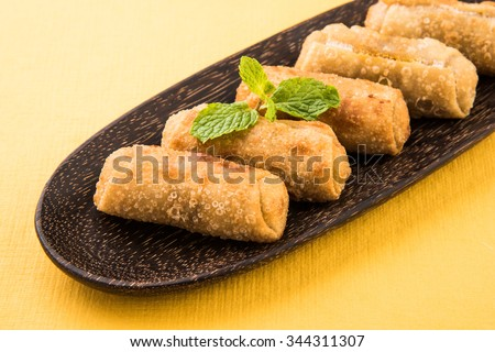 veg roll in brown wooden oval plate with mint leaf, cropped view on yellow background, top view