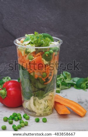 Vegetable salad in take away clear plastic cup. Selective focus, copy space