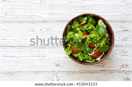 Vegetable salad with fresh lettuce, tomatoes and cucumber in clay pot. Top view.
