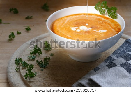 Vegetable soup with a little splash cream in a white Porcelain bowl on rustic board