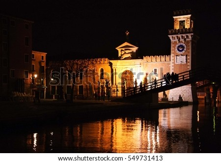 Venetian Arsenal at night. People on the bridge going to Carnival events taking place inside the Arsenale. Venice (Italy). Selective focus on the clock tower.