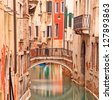 Venice, bridge on water canal and traditional architecture in a long exposure photography. - stock photo