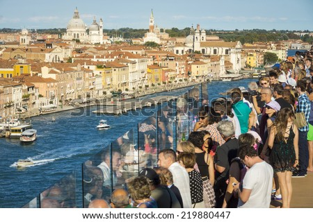 VENICE, ITALY - AUGUST 17, 2014: passengers of a large cruise boat gathered in the late afternoon to enjoy the view over this famous city in northern Italy