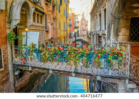 Venice, Italy - 10 February 2016: A bridge with Bouquet of Flowers over a narrow canal in Venice, Italy.
