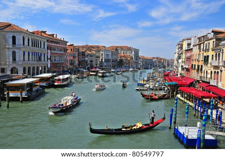 VENICE, ITALY - JUNE 19: Tourists traveling on gondola and vaporetto water bus on Grand Canal on June 19, 2011 in Venice, Italy. Venice has an average of 50,000 tourists a day.