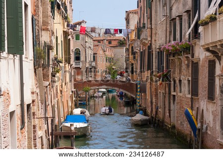 Venice, Italy - June 21, 2014: Typical view of a narrow canal with boat, bridge and old houses of Venice, Italy. With people.