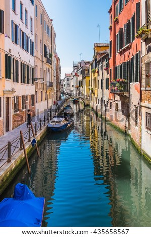 Venice, Italy - 7 June 2016: Woman walks along a quiet canal side through the residential back streets of Venice, Italy