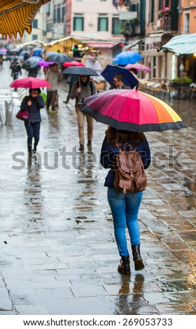 VENICE , ITALY - MARCH 22, 2015: people walking with umbrellas in the rainy city