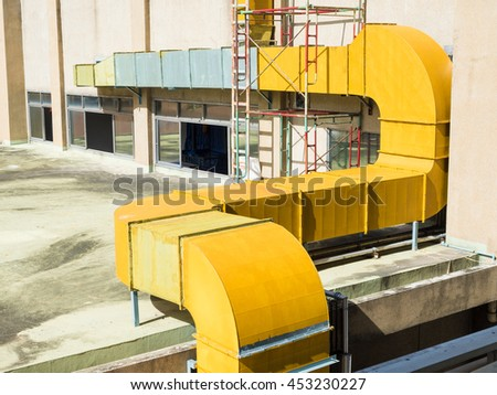 ventilating metal duct with yellow painted on the buildings roof
