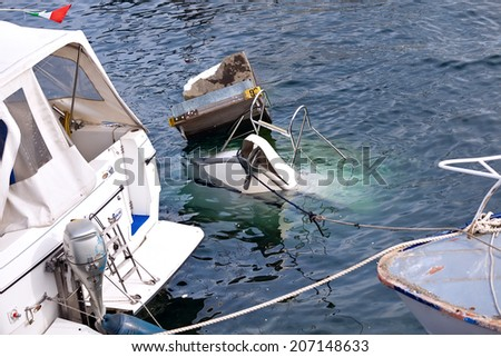 VERBANIA, LAGO MAGGIORE, ITALY - OCTOBER 12, 2013: Damage and salvage efforts from a thunderstorm which destroys town's marine piers with luxury yachts and motorboats.