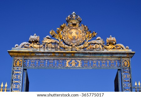 VERSAILLES, FRANCE - April 19, 2015: Golden Main Gates of the Versailles Palace. The Palace Versailles was a royal chateau. It was added to the UNESCO list of World Heritage Sites. Paris, France.