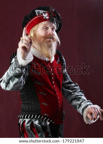 vertical full length portrait of an adult male with a beard and mustache in medieval costume and headdress studio on a burgundy background