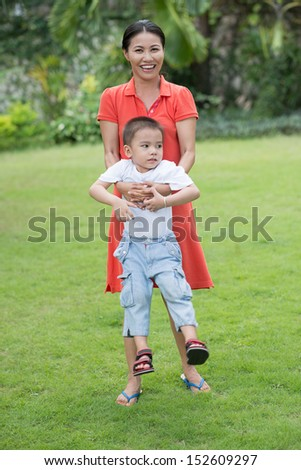 Vertical image of a mum playing with her son on the green lawn