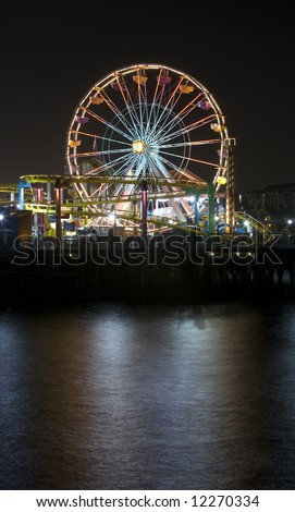 Vertical image of the famous Pacific Wheel at Santa Monica Pier in Southern California with a roller coaster ride in the foreground