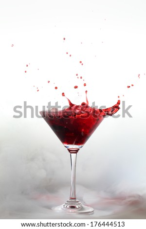 Vertical photo of a splash colored drink with smoke
