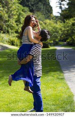 Vertical photo of young adult man lifting his lady with walking path, green grass and trees in background