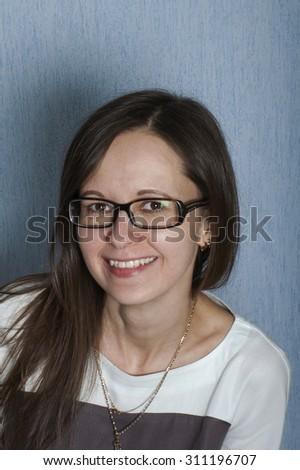 Vertical studio portrait of a friendly looking mid aged woman with tilted head
