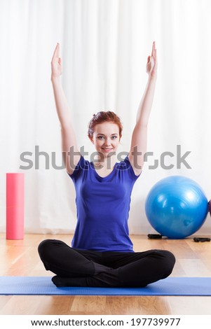 Vertical view of a fit young woman doing yoga exercise