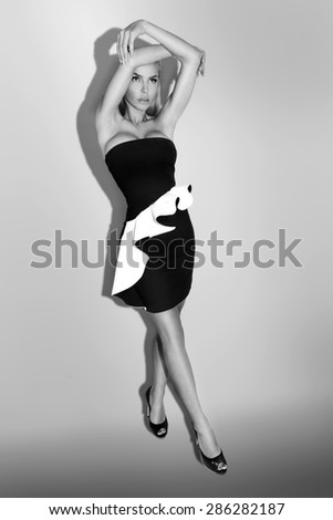 Very beautiful sexy blond-haired woman in a sexy short black & white dress with long legs standing on a white background holding hands above his head