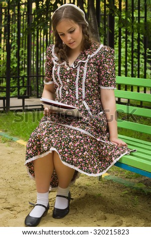 Very beautiful soviet girl in retro style with a music book sitting on a bench in the park
