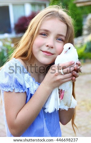 very beautiful young girl with a white dove of peace in his hands hugging him in a blue blouse