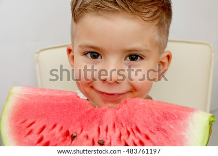 Very handsome cute small blond boy with fashionable hairdo is eating red juicy ripe watermelon