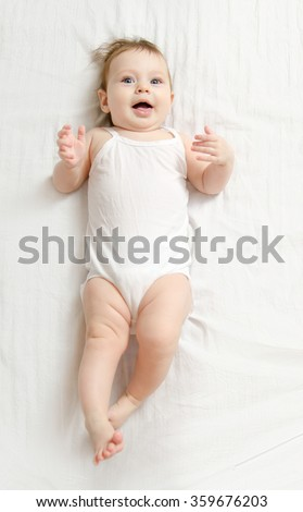 Very happy laughing baby in white body suit lying on his back on the white sheet and show his tongue.