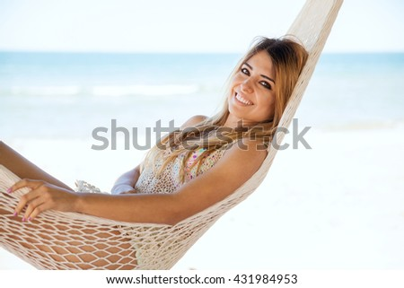Very relaxed young woman laying on a hammock during her vacation at the beach and smiling