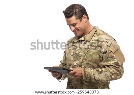 Veteran soldier | Smiling army soldier looking down at digital tablet in front of white background