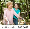 Vibrant senior lady with walker and hearing aid laughing with her teen-aged granddaughter. - stock photo