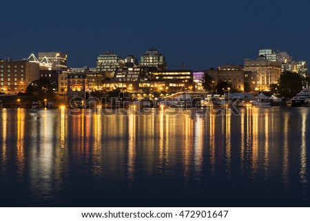 VICTORIA, BC, CANADA - AUG 16 2016. Victoria's charm and beauty has a lot to offer for any world traveler. Street lights reflect in water at Inner Harbor
