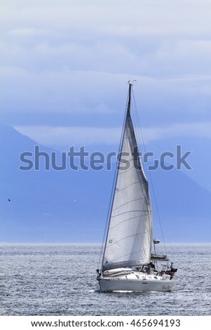 VICTORIA, BC CANADA - JULY 29 2016:A sailboat alone on the ocean with ripples of waves mountains in the backgrounds..