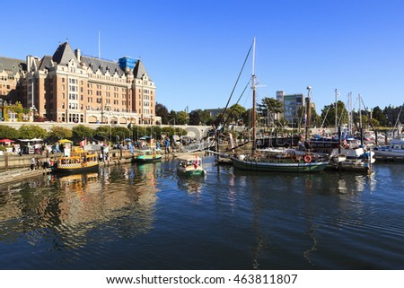 VICTORIA CANADA  JULY 27 2016: Enjoy a relaxed stroll on the boardwalk around the Inner Harbour of BCâ??s capital city of Victoria, steps from waterfront attractions, the landmark Parliament Buildings,