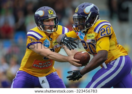 VIENNA, AUSTRIA - JULY 13, 2014: QB Christoph Gross (#8 Vikings) hands off the ball to RB Islaam Amadu (#20 Vikings) during an Austrian football league game.