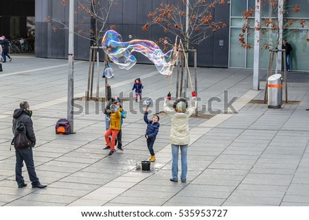 VIENNA, AUSTRIA - NOVEMBER 13, 2016: Children are playing with bubbles for fun in the city park in Vienna, Austria.