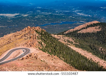 View for Pikes Peak of winding highway down into the valley with lake in the distance