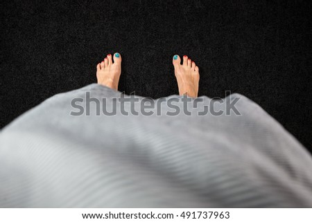 View from above a woman feet with colorful nails on black background.