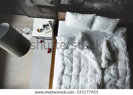 View from above at the bed with white pillows and blankets. There is a white table with book and cup, lamp with lampshade, wardrobe with glass sliding doors. On the floor there is parquet with carpet.