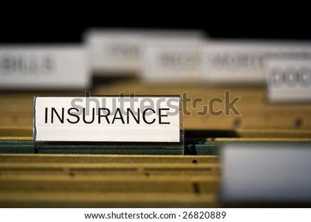 "view inside filing cabinet with brown file folders, green folder with ""insurance"" label in focus"