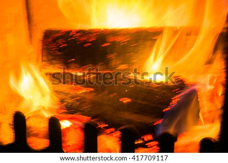View of a roaring fire within a large stone fireplace, background.