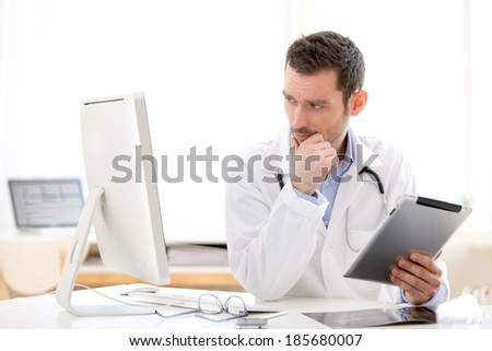 View of a young doctor using tablet at work