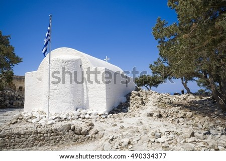 View of Agios Panteleimonas Church built on top of craggy rock on west coast of Rhodes Island, castle in Monolithos, Greece