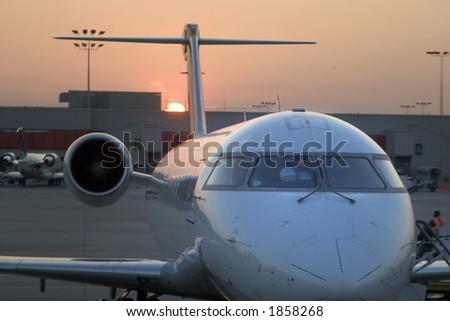 View of an airplane at the gate during sunset