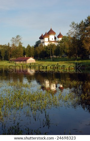 View of ancient cathedral with reflection in water, Kargopol town, north Russia