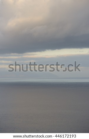 View of blurred sunshine reflections in ocean and clouds over Gomera Island from Los Gigantes, Tenerife, Canary Islands, Spain.
