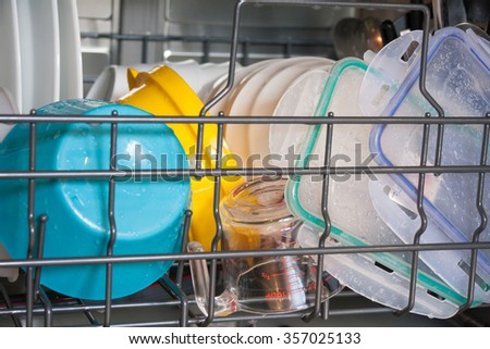 View of bottom rack of dishwasher loaded with plastic ware still wet