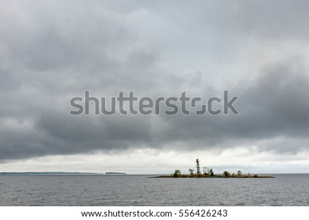 View of isle with lighthouse in Russian Karelia from the waters of Onega lake