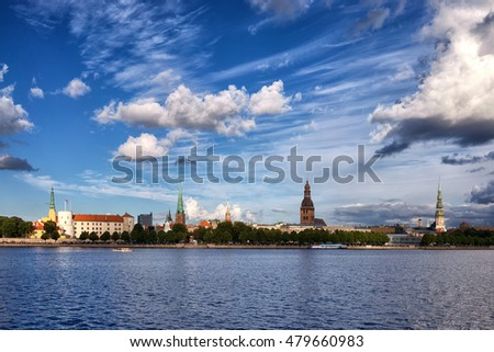 View of the city of Riga on the bank of the Daugava River with spiers of cathedrals and churches under the blue summer sky with clouds