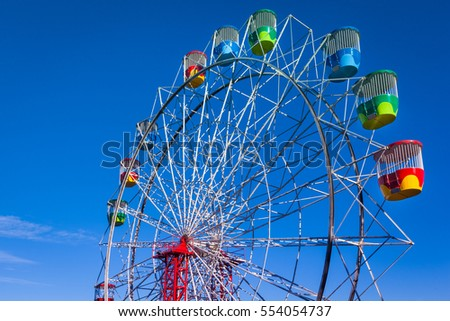 View of the colorful Ferris Wheel of the Sydney Luna Park against blue sky